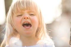 Portrait grimaçant extérieur de sourire heureux de jeune de bébé vraie de personnes fin blonde caucasienne de fille Photographie stock