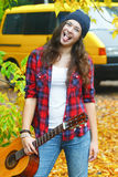 Portrait of grimacing guitar player girl wearing slouchy beanie hat at yellow van background Royalty Free Stock Images