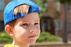 Portrait of a grinning boy wearing blue baseball cap royalty free stock image