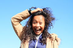 Portrait of grinning girl. Young tropical woman - grinning Papuan girl holding her long black curly hair with blue sky behind royalty free stock image