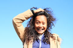 Portrait of grinning girl. Young tropical woman - grinning Papuan girl holding her long black curly hair with blue sky behind stock photo