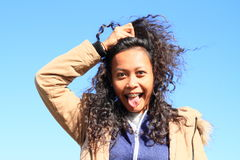 Portrait of grinning girl. Young tropical woman - grinning Papuan girl with tongue out of mouth holding her long black curly hair with blue sky behind royalty free stock image