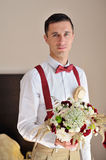 Portrait of the groom with a bouquet in hands Stock Photography