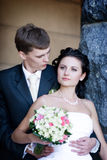 A portrait of the groom and the bride by the stone Royalty Free Stock Images