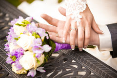 Portrait of groom holding brides hand on table near bouquet Royalty Free Stock Photo