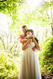 Portrait of groom hugging bride under tree at park Royalty Free Stock Photo