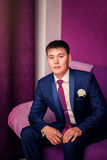Portrait of groom indoors in purple interior Stock Photos