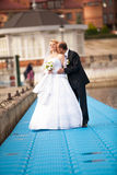 Portrait of groom kissing bride on pier near river Stock Photo