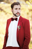 Portrait of the groom, red suit with a buttonhole flower. Wedding in style Marsala color. Royalty Free Stock Photo
