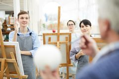 Art Students Listening in Lecture. Portrait of group of cheerful art students standing in row at easels and listening to teacher during lecture in class stock photography