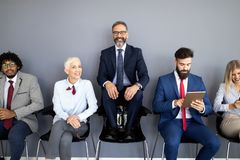 Portrait of group of diverse corporate colleagues standing in a row together at a table in a bright modern office stock image