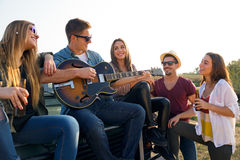 Portrait of group of friends playing guitar and drinking beer. Royalty Free Stock Photos