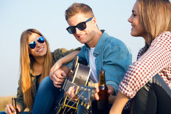 Portrait of group of friends playing guitar and drinking beer. Stock Photo