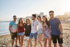 Group of friends standing together on beach smiling. Portrait of group of friends standing together on beach smiling royalty free stock image