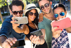 Portrait of group friends taking photos with a smartphone. Stock Photos