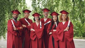 Portrait of group of graduating students holding diplomas and standing outdoors with arms crossed wearing gowns and stock footage