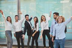 Group of happy coworkers raising hands in front of building royalty free stock images