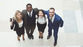 Portrait of group of happy and diverse business people who are standing together. They jump in the air and cheer to Stock Image