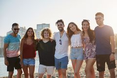 Group of happy friends standing together on beach stock photo
