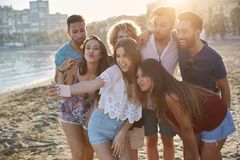 Group of happy friends taking selfie on beach royalty free stock images