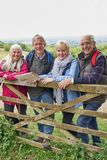 Portrait Of Group Of Senior Friends Hiking In Countryside Standing By Gate royalty free stock images