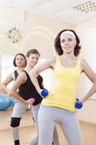 Portrait of Group of Three Caucasian Female Athletes Having a Workout Training with Barbells Indoors Royalty Free Stock Image