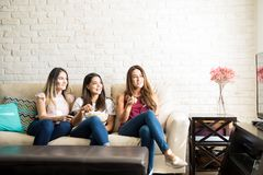 Group of friends watching a movie. Portrait of a group of three friends having some fun watching a movie on tv at home. Lots of copy space Stock Image