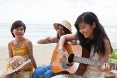 Portrait group of young asian woman palying guitar in sea beach Royalty Free Stock Photography