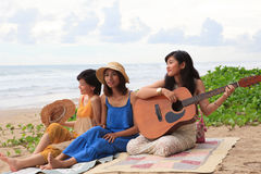 Portrait group of young asian woman playing guitar in sea beach Stock Photo