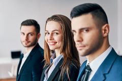 Portrait of group of young business people in a row in office. stock photo