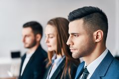 Portrait of group of young business people in a row in office. royalty free stock photos