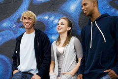 Portrait of a group of young friends hanging out in front of a graffiti covered wall Royalty Free Stock Photography