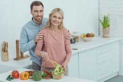 portrait of grown son hugging mother while cooking dinner together stock photography