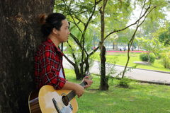 Portrait of guitarist or musician is playing acoustic guitar in the beautiful nature park background. Royalty Free Stock Photos