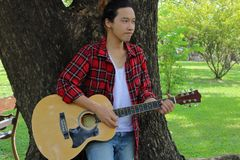 Portrait of guitarist playing music on acoustic guitar in the park background. Royalty Free Stock Image