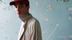 Portrait of a guy in a baseball cap. Fashion. Portrait of a young guy in a red baseball cap and raincoat. Fashion portrait of the model. A man in a white shirt Royalty Free Stock Photography