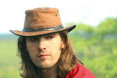 Portrait of guy with  in cowboy hat. Country style. Safari. Romance. Royalty Free Stock Image