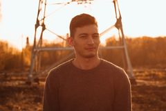 Portrait of a guy in the field on a sunset background royalty free stock photography