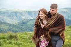 Portrait of a guy with a girl covered up with a rug embrace along a country road. Portrait of a guy with a girl covered up with a rug go in an embrace along a Stock Photography
