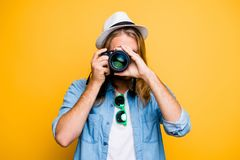 Portrait of guy in hat looking at photo camera, shooting photogr. Aphs during excursion, making photosession over yellow background Royalty Free Stock Photos