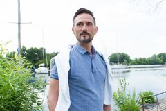 Portrait of guy near of river with boats. Handsome man before sailing on river. Man`s style, dressing polo and goatee royalty free stock photos