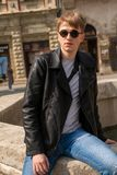 Portrait of a guy in round sunglasses and leather jacket. In Europe town royalty free stock photos