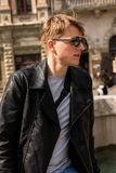 Portrait of a guy in round sunglasses and leather jacket. In Europe town royalty free stock image