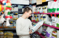 Portrait of  guy selecting vet food in petshop Royalty Free Stock Photography