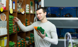 Portrait of guy selecting vet food in petshop. Portrait of happy guy selecting vet food in petshop Royalty Free Stock Photos