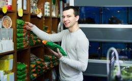 Portrait of guy selecting vet food in petshop. Portrait of happy american guy selecting vet food in petshop Stock Photography