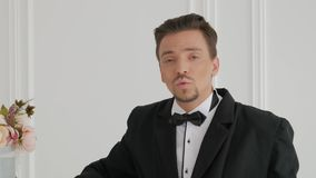 Portrait of guy sings in luxury room. Portrait of stylish guy singer in costume sings against the backdrop of a bright and luxury wall with flowers in a retro stock video
