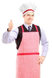 A portrait of a guy wearing apron and giving thumb up Royalty Free Stock Photo