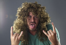 Portrait of a guy with a wig doing a rock and roll symbol.  Royalty Free Stock Photos