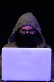 Portrait of hacker with laptop on dark background Royalty Free Stock Photo